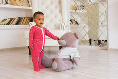Happy baby boy playing with his teddy bear.  Stock Image