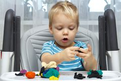 Happy baby boy playing with plasticine. A two-year-old toddler sits in the baby chair and moldes something with a clay stock images