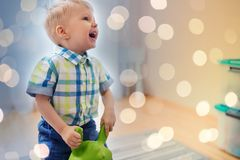 Happy baby boy playing with ride-on toy at home. Childhood, toys and people concept - happy little baby boy playing with ride-on toy horse at home Royalty Free Stock Photo