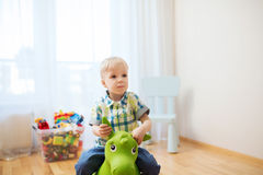 Happy baby boy playing with ride-on toy at home Royalty Free Stock Image