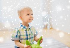Happy baby boy playing with ride-on toy at home. Childhood, toys and people concept - happy little baby boy playing with ride-on toy horse at home over snow Royalty Free Stock Photos