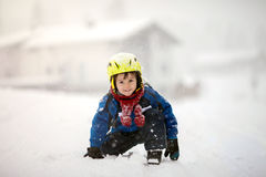 Happy baby boy playing in the snow. Happy little boy playing in the snow while snowing, helmet, scarf and gloves Stock Photography