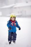 Happy baby boy playing in the snow. Happy little boy playing in the snow while snowing, helmet, scarf and gloves Stock Images