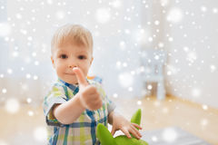 Happy baby boy playing with toy showing thumbs up. Childhood, toys and people concept - happy little baby boy playing with ride-on toy horse and showing thumbs Royalty Free Stock Images