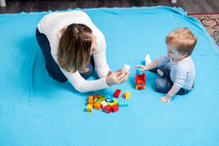 Happy baby boy playing with toys next to her mother Stock Photos