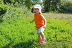 Happy baby boy running outdoors in summertime Royalty Free Stock Photo