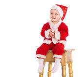 Happy baby boy in santa costume sit on chair Royalty Free Stock Photography
