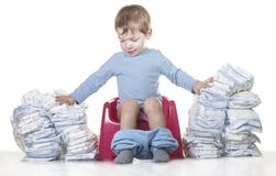 Happy baby boy sitting on chamber pot tearing down diaper piles Royalty Free Stock Images