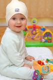 Happy baby boy sitting with his toys. In the room Royalty Free Stock Photos