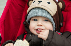 Happy baby boy sitting in a red stroller Royalty Free Stock Image