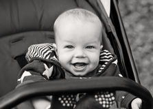 Happy baby boy sitting in a stroller Royalty Free Stock Photo