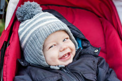 Happy baby boy sitting in a stroller Stock Image