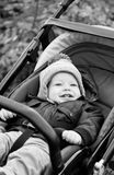 Happy baby boy sitting in a stroller Stock Photography