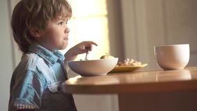 Happy baby boy spoon eats itself. Little boy sitting at the table and eating milk snack. Baby eating food on kitchen. Childcare. Little boy sitting at the stock footage