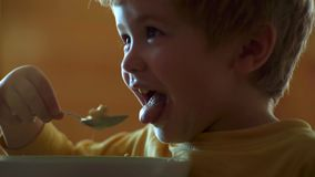 Happy baby boy spoon eats itself. Little baby are eating close up portrait. stock footage