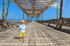 Happy baby boy walk by wood bridge to ocean beach stock photo