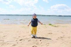 Happy baby boy walking on riverside Stock Photos