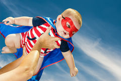Happy baby boy wearing superhero costume flying. In the sky Stock Images