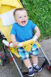 Happy baby boy on yellow baby carriage Stock Images