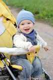 Happy baby boy on yellow baby carriage outdoors Royalty Free Stock Images