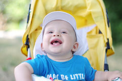 Happy baby boy on yellow baby carriage in summer Stock Image