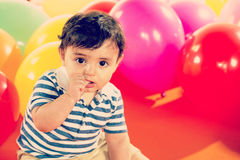 Happy baby boy with yellow ballons. Boy playing with colorful balloons over white Royalty Free Stock Photography