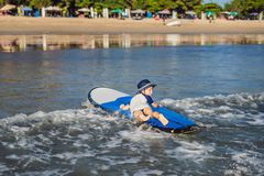 Happy baby boy - young surfer ride on surfboard with fun on sea waves. Active family lifestyle, kids outdoor water sport. Lessons and swimming activity in surf royalty free stock image