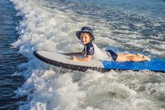 Happy baby boy - young surfer ride on surfboard with fun on sea waves. Active family lifestyle, kids outdoor water sport. Lessons and swimming activity in surf stock images