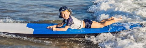Happy baby boy - young surfer ride on surfboard with fun on sea waves. Active family lifestyle, kids outdoor water sport lessons a. Nd swimming activity in surf royalty free stock image