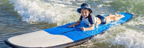 Happy baby boy - young surfer ride on surfboard with fun on sea waves. Active family lifestyle, kids outdoor water sport lessons a. Nd swimming activity in surf royalty free stock photos