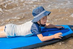 Happy baby boy - young surfer ride on surfboard with fun on sea. Waves. Active family lifestyle, kids outdoor water sport lessons and swimming activity in surf stock photography