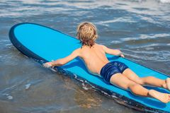 Happy baby boy - young surfer ride on surfboard with fun on sea. Waves. Active family lifestyle, kids outdoor water sport lessons and swimming activity in surf royalty free stock photography