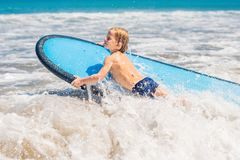 Happy baby boy - young surfer ride on surfboard with fun on sea. Waves. Active family lifestyle, kids outdoor water sport lessons and swimming activity in surf royalty free stock images