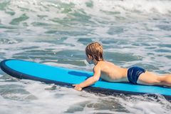 Happy baby boy - young surfer ride on surfboard with fun on sea waves. Active family lifestyle, kids outdoor water sport. Lessons and swimming activity in surf stock photography