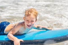 Happy baby boy - young surfer ride on surfboard with fun on sea waves. Active family lifestyle, kids outdoor water sport. Lessons and swimming activity in surf royalty free stock images