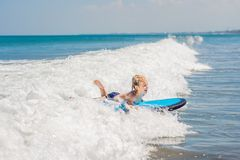 Happy baby boy - young surfer ride on surfboard with fun on sea waves. Active family lifestyle, kids outdoor water sport. Lessons and swimming activity in surf stock image