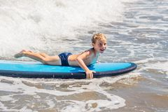 Happy baby boy - young surfer ride on surfboard with fun on sea waves. Active family lifestyle, kids outdoor water sport. Lessons and swimming activity in surf royalty free stock photo
