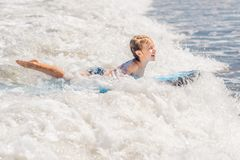 Happy baby boy - young surfer ride on surfboard with fun on sea waves. Active family lifestyle, kids outdoor water sport. Lessons and swimming activity in surf stock photo