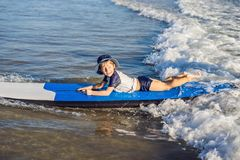 Happy baby boy - young surfer ride on surfboard with fun on sea waves. Active family lifestyle, kids outdoor water sport. Lessons and swimming activity in surf royalty free stock photography
