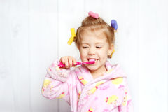 Happy baby brushing teeth. Little girl brushing her teeth in curlers stock photo