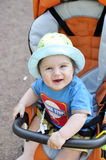 Happy baby in buggy. Baby in buggy in hat smiling Royalty Free Stock Image