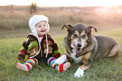 Happy Baby Bundled up Outside in Winter with Pet Dog. An adorable 8 month old baby girl is bundled up in a sweater and wearing a winter earflap hat looking Royalty Free Stock Photo