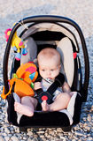 Happy baby in the car seat. Baby in the car seat on the beach on a sunny day stock photos