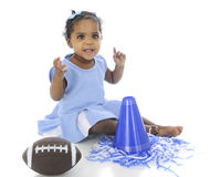 Happy Baby Cheerleader. An adorable baby in her cheerleading outfit, happily sitting with her pompoms, megaphone and football.  On a white background Royalty Free Stock Images