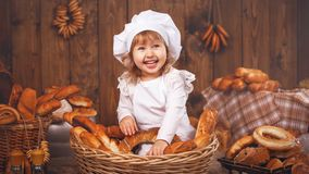 Happy baby chef in wicker basket laughing playing chef in bakery, lots of bread baking. stock images