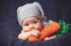 Happy baby child in costume a rabbit bunny with carrot on a grey. Background Royalty Free Stock Photos