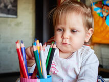 Happy baby child draws with colored pencils crayons Royalty Free Stock Photography