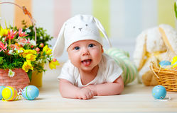 Happy baby child with Easter bunny ears and eggs and flowers Stock Photos