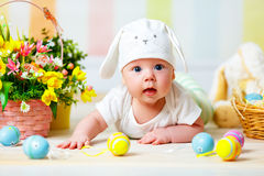 Happy baby child with Easter bunny ears and eggs and flowers. Happy baby child with Easter bunny ears and colorful eggs and flowers stock image