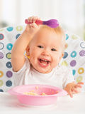 Happy baby child eats itself with a spoon. Cheerful happy baby child eats itself with a spoon royalty free stock image